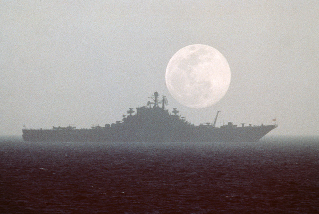 A silhouetted starboard beam view of a Soviet Kiev class aircraft carrier (CVHG)