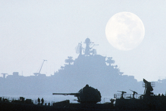 A silhouetted starboard view of the Soviet aircraft carrier KIEV (CVHG) as seen across the fore deck of a Sovremenny class destroyer under a full moon