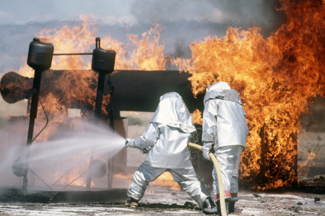 Airmen from the base fire protection branch extinguish a simulated aircraft fire during a training exercise.  The firemen are wearing aluminized proximity suits