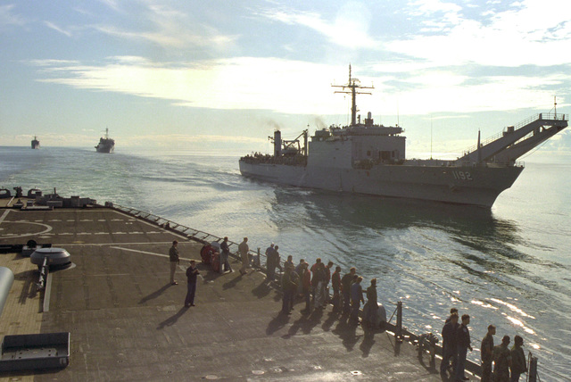 "The tank landing ship USS SPARTANBURG COUNTY (LST-1192) pulls alongside the battleship USS IOWA (BB-61) during ""leapfrog"" maneuvering drills with the IOWA. The ships are en route to NATO exercise NORTHERN WEDDING '86"