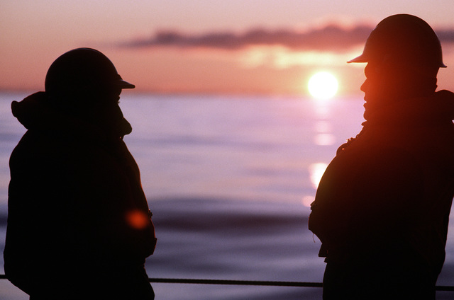 Two sailors aboard the battleship USS IOWA (BB-61) wait for early evening underway replenishment to begin during operation Northern Wedding