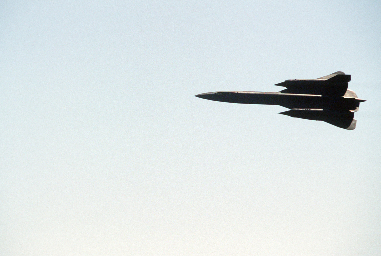 An air-to-air top view of an SR-71 aircraft banking left while performing at an international air show