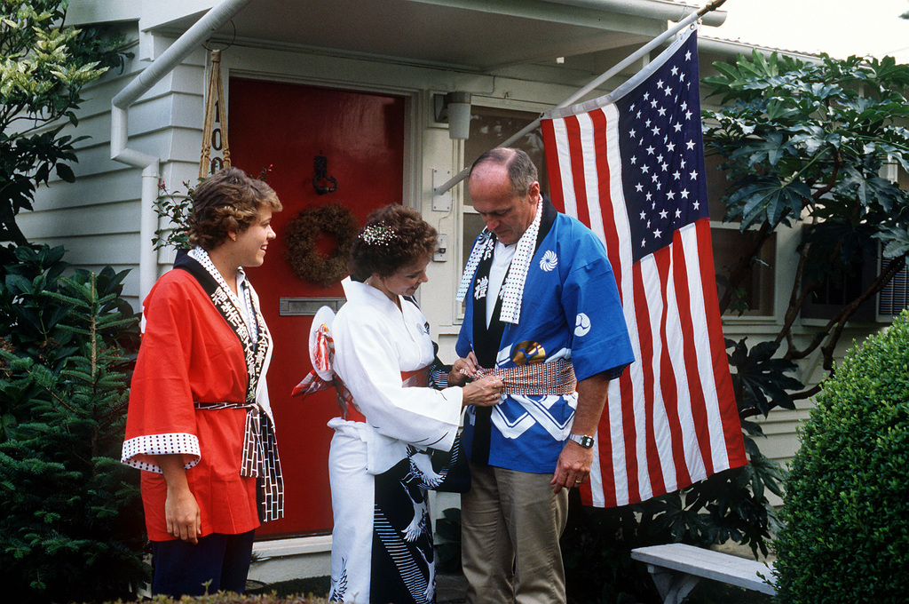 Judy Frey, wife of Colonel Edward P. Frey, Commander, 475th Air Base Wing, straightens her husband's happi coat in front of their house while their daughter Lisa watches. The colonel and his family will be attending the Tanabata Festival, an annual celebration by the people of Fussa City just outside the base