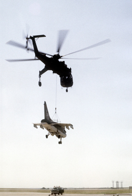 A CH-54 Tahre helicopter airlifts an A-7 Corsair II aircraft