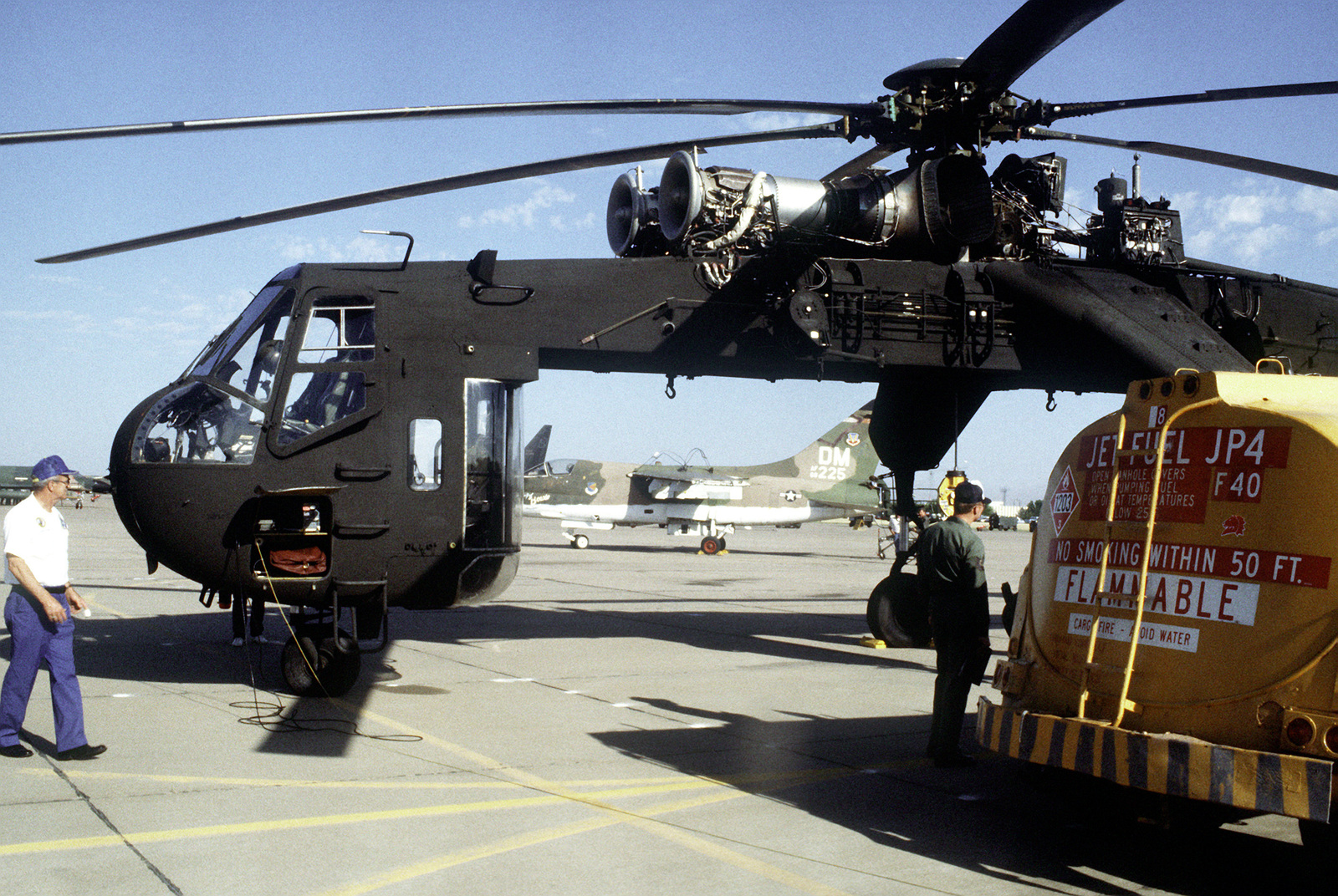 A CH-54 Tahre helicopter is refueled on the flight line before airlifting an A-7 Corsair II aircraft