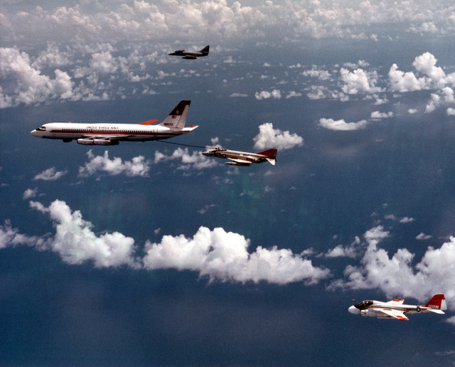 An air-to-air left side view of a UC-880 Convair aircraft assigned to the Naval Air Test Center (NATC), Naval Air Station, Patuxent River, refueling an NATC F-4 Phantom II aircraft. Also standing by are a TA-4J Skyhawk aircraft, background, and an NATC A-6 Intruder aircraft, foreground