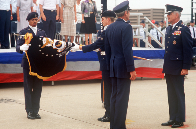 Members of the color guard roll up the flag of the 314th Air Division during a ceremony marking the deactivation of the 314th Air Division and the reactivation of the 7th Air Force. General (GEN) Robert W. Bazley, commander, Pacific Air Forces and Major General (MGEN) James T. Callaghan, commander, Republic of Korea/US Combined Forces Command stand at attention during the ceremony