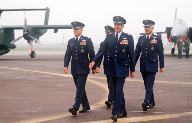 Officers march down the flight line past an OV-10 Bronco and an F-15 Eagle aircraft during a ceremony marking the deactivation of the 314th Air Division and the reactivation of the 7th Air Force. (GEN) Robert W. Bazley, commander, Pacific Air Forces, and Colonel (COL) James L. Altemose are followed by Major General (MGEN) James T. Callaghan, commander, Republic of Korea/US Combined Forces Command; and Lieutenant General (LGEN) Jack T. Gregory, new commander, 7th Air Force
