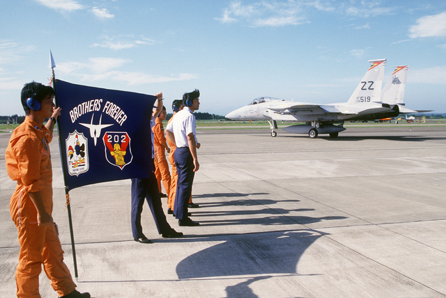 Japanese pilots display a banner bearing the emblems of the 67th Tactical Fighter Squadron and the host unit of the Japan Air Self-Defense Force on the flight line as a 67th TFS F-15 Eagle aircraft prepares for takeoff at the close of Exercise COPE NORTH 86-4.  US Air Force squadrons engaged in dissimilar air combat training with Japan Air Self-Defense Force squadrons during the exercise