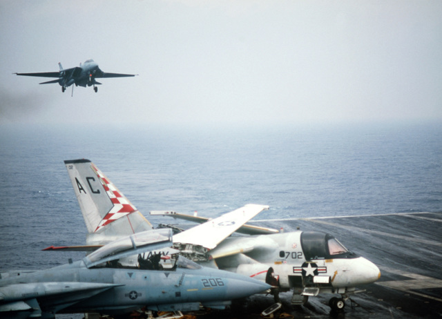 A Fighter Squadron 14 (VF-14) F-14A Tomcat aircraft approaches for a landing aboard the aircraft carrier USS JOHN F. KENNEDY (CV 67) during NATO Exercise DISPLAY DETERMINATION '86. An S-3A Viking aircraft and another F-14 are parked on the flight deck