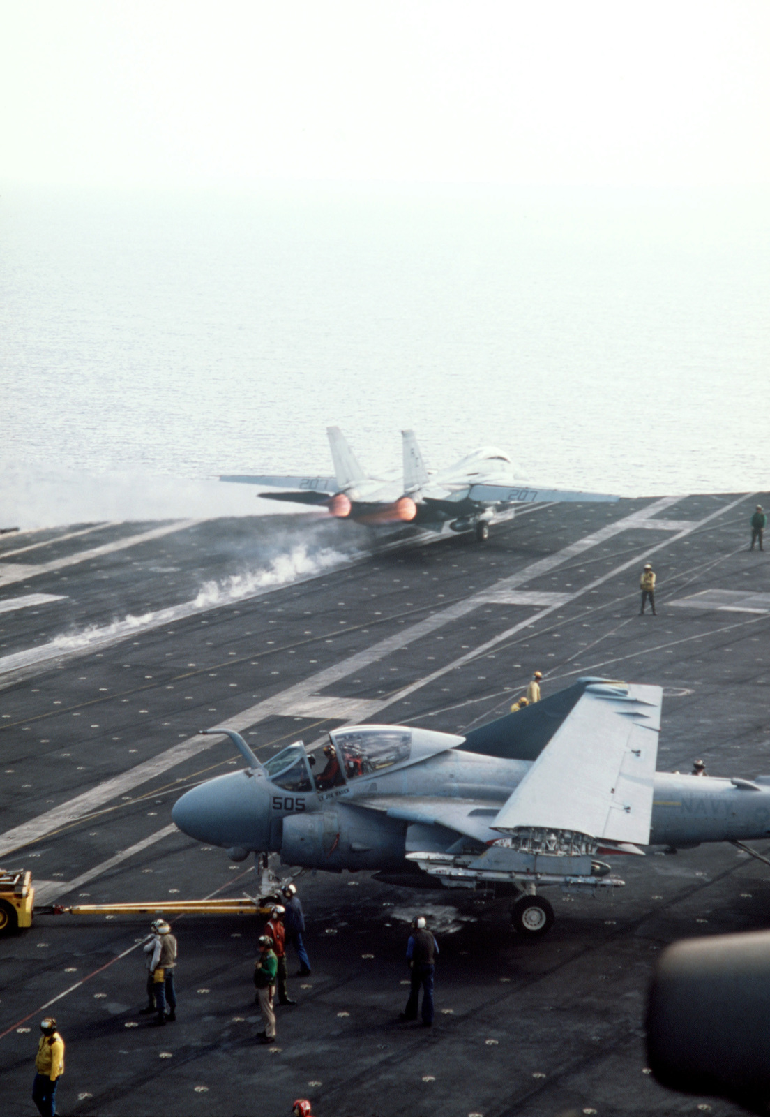 A Fighter Squadron 32 (VF-32) F-14A Tomcat aircraft is launched from the aircraft carrier USS JOHN F. KENNEDY (CV 67) during NATO Exercise DISPLAY DETERMINATION '86. An A-6E Intruder aircraft is being towed by an MD-3A tow tractor