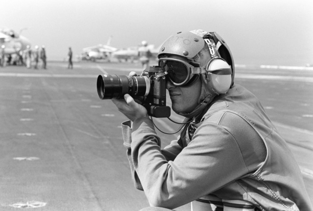 A photographer's mate concentrates on his subject aboard the aircraft carrier USS JOHN F. KENNEDY (CV 67) during NATO Exercise DISPLAY DETERMINATION '86