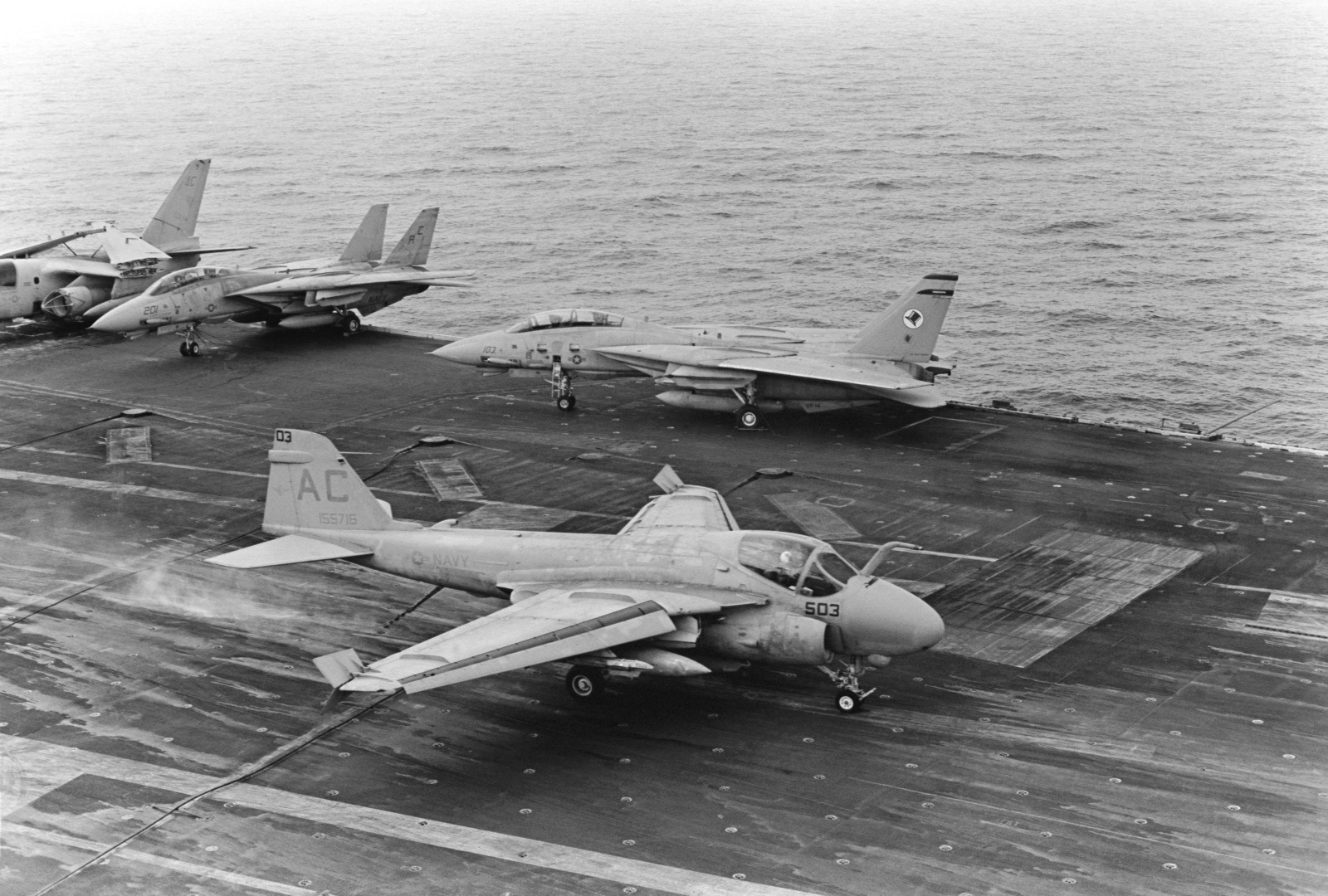 An A-6E Intruder aircraft lands aboard the aircraft carrier USS JOHN F. KENNEDY (CV 67) during NATO Exercise DISPLAY DETERMINATION '86. Several F-14A Tomcat aircraft are parked on the flight deck in the background