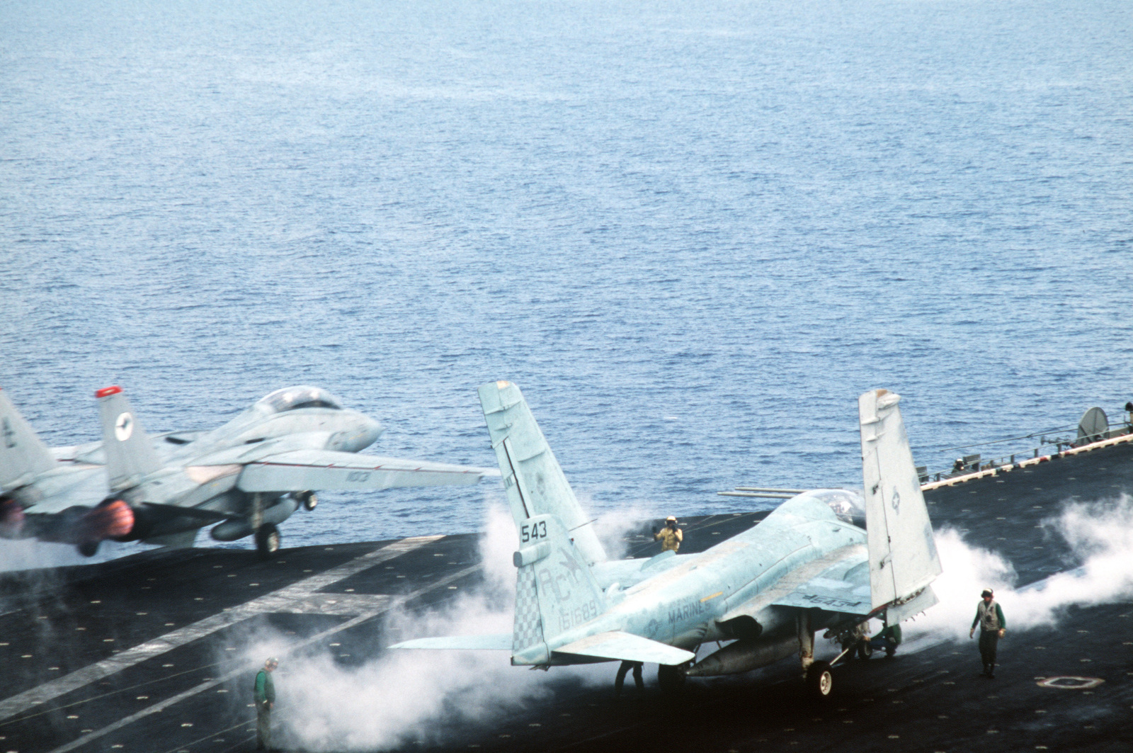 An A-6E Intruder is positioned on a catapult as an F-14A Tomcat aircraft is launched from the aircraft USS JOHN F. KENNEDY (CV 67) during NATO Exercise DISPLAY DETERMINATION '86