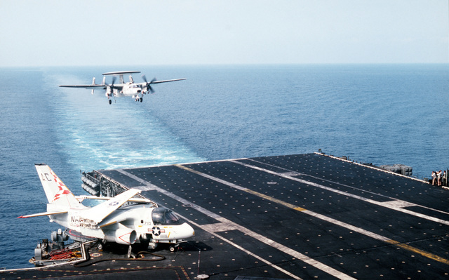 An Airborne Early Warning Squadron 126 (VAW-126) E-2C Hawkeye aircraft approaches for a landing aboard the aircraft carrier USS JOHN F. KENNEDY (CV 67) during NATO Exercise DISPLAY DETERMINATION '86. An S-3A Viking aircraft is parked on deck