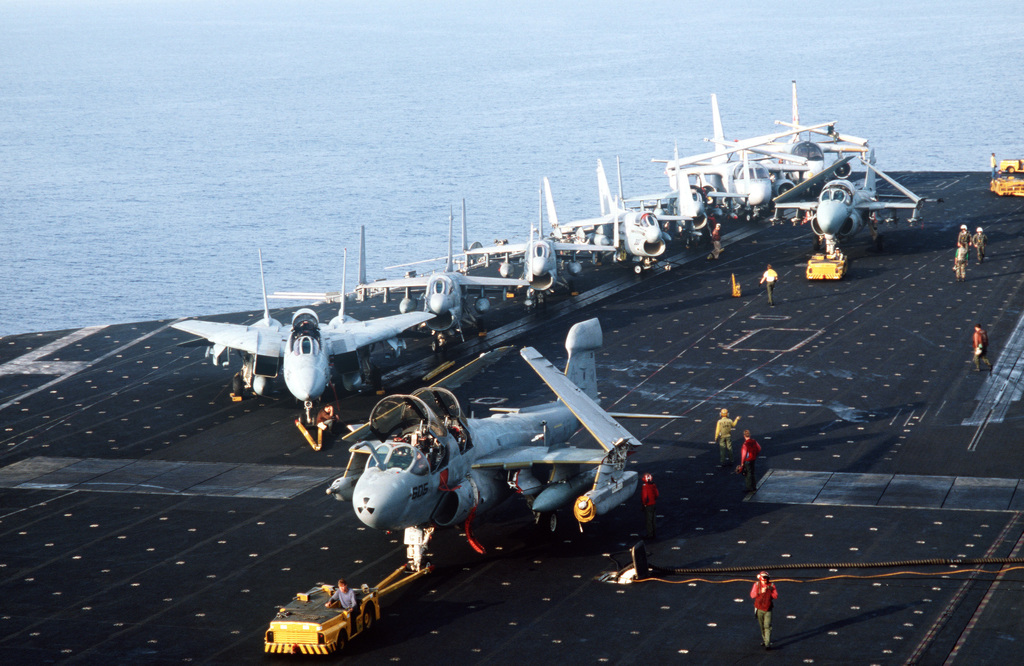 An EA-6 Prowler aircraft is towed by an MD-3A tow tractor on the flight deck of the aircraft carrier USS JOHN F. KENNEDY (CV 67) during NATO Exercise DISPLAY DETERMINATION '86. F-14A Tomcat, A-7E Corsair II and S-3A Viking aircraft are in the background