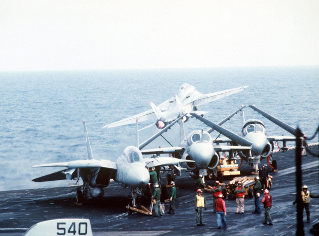 An F-14A Tomcat aircraft clears the deck of the aircraft carrier USS JOHN F. KENNEDY (CV 67) during NATO Exercise DISPLAY DETERMINATION '86. Another F-14 and two A-6E Intruder aircraft are being serviced on the flight deck