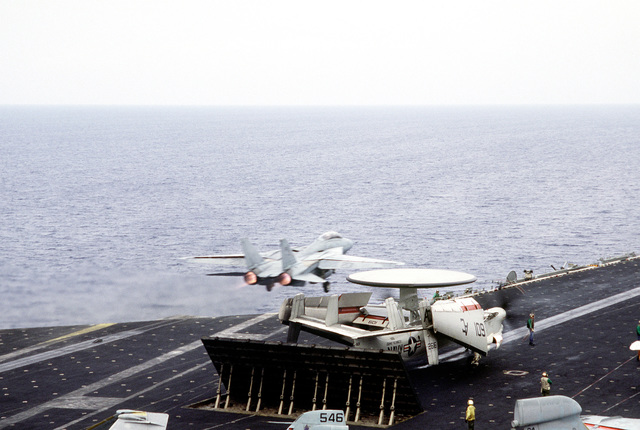 An F-14A Tomcat aircraft is launched from the aircraft carrier USS JOHN F. KENNEDY (CV-67) during NATO exercise Display Determination '86. An E-2C Hawkeye aircraft is parked in front of a Mark 7 blast deflector