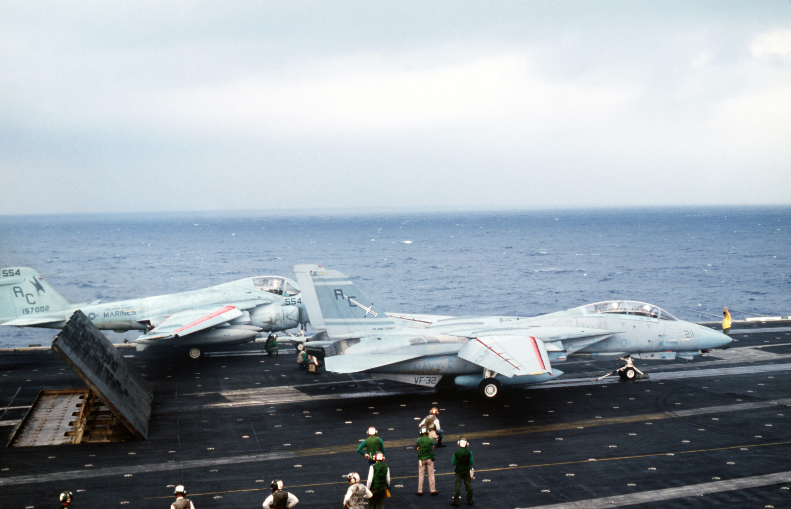 Flight deck crewmen signal launch instructions to the pilot of a Fighter Squadron 32 (VF-32) F-14A Tomcat aircraft aboard the aircraft carrier USS JOHN F. KENNEDY (CV 67) during NATO Exercise DISPLAY DETERMINATION '86. An A-6E Intruder aircraft is on the catapult in the background
