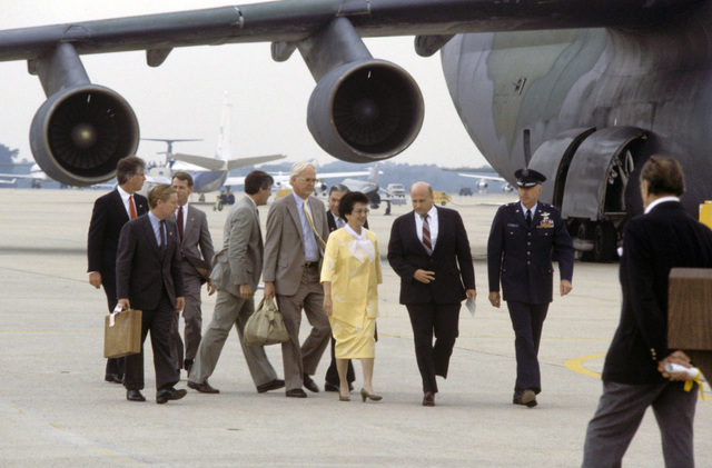 Philippine President Corazon Aquino, accompanied by Richard L. Armitage, assistant secretary of defense for international security affairs, and several US and Filipino officials, approaches the speakers podium. President Aquino has arrived to show her appreciation for US Air Force humanitarian airlift operation support efforts