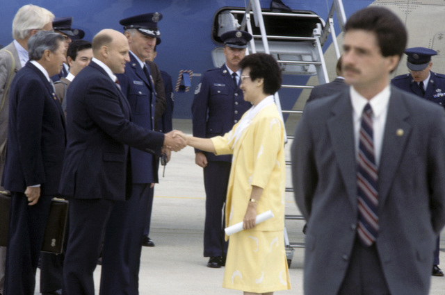 Philippine President Corazon Aquino shakes hands with the US Assistant Secretary of Defense for International Security Affairs Richard L. Armitage upon her arrival at the base. President Aquino has arrived for a ceremony honoring US Air Force efforts to supply humanitarian aid to the people of the Philippines