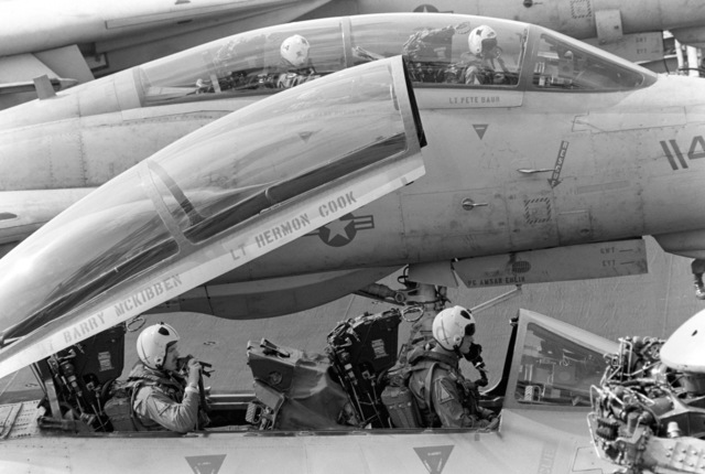 Pilots and radar intercept officers wait in the cockpits of their F-14A Tomcat aircraft during flight operations aboard the aircraft carrier USS JOHN F. KENNEDY (CV 67). They are participating in NATO Exercise DISPLAY DETERMINATION '86