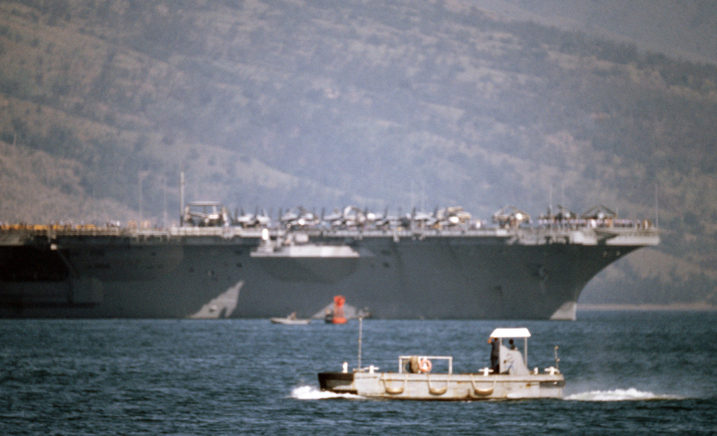 A harbor utility craft passes the nuclear-powered aircraft carrier USS CARL VINSON (CVN 70), background, as it enters port