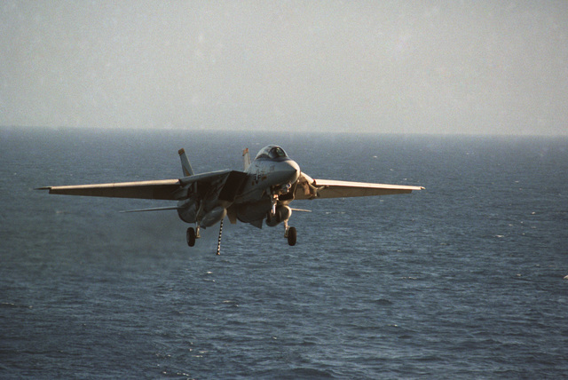A US Navy (USN) F-14A Tomcat, Fighter Squadron 21 (VF-21), Freelancers, Naval Air Station (NAS) Yokosuka, Japan, with gear down, flaps down and tail hook down, as it comes in for a landing on an aircraft carrier at sea