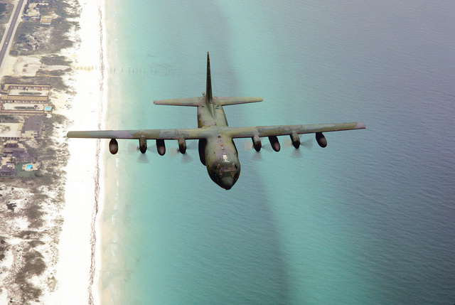 Air to air front, top view of an Air Mobility Command's C-130 Hercules flying over the Gulf coastline near Eglin AFB, Florida. Exact Date Shot Unknown