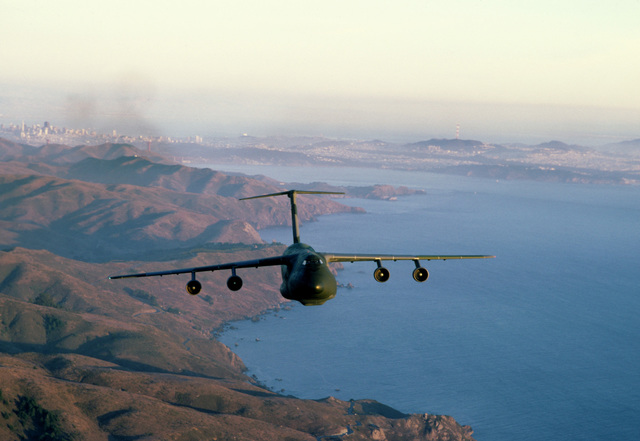 Air to air front view of Air Mobility Command's 60th Military Airlift Wing's C-5 Galaxy flying over the coastline, with San Francisco and bay in background, during training mission out of Travis, AFB, California. Exact Date Shot Unknown