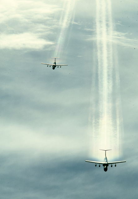 Air to air top, front view of two Air Mobility Command's C-141 Starlifters with contrails flying in formation during a training mission. Exact Date Shot Unknown