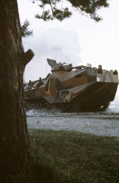 An LVTP7 tracked landing vehicle lays down a smoke screen while coming ashore during the NATO amphibious Exercise NORTHERN WEDDING '86