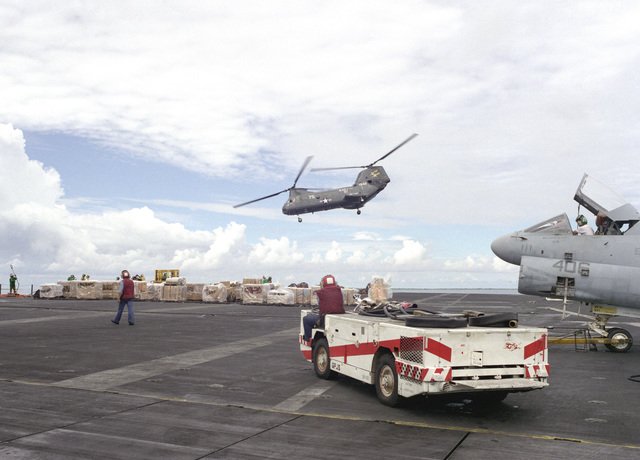A flight deck crewman stands by in a crash vehicle as a Helicopter Combat Support Squadron 11 (HC-11) CH-46 Sea Knight helicopter transports supplies to the deck of the nuclear powered aircraft carrier USS CARL VINSON (CVN-70) in preparation for operations in the North Arabian Sea