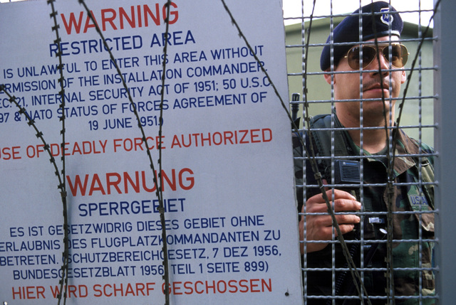 A member of the 50th Security Police Squadron stands behind a barbed wire fence in a weapons storage area. A sign in German and English warns that the area is restricted to authorized personnel only. Security police are preparing the base for a scheduled mass demonstration against the construction of an American cruise missile base at nearby Wuescheim