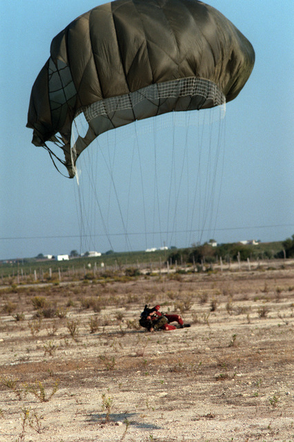A member of the Explosive Ordnance Disposal (EOD) Team lands in the drop zone during an EOD Team/Sea-Air-Land (SEAL) Team joint parachuting exercise near Naval Air Station, Rota, Spain