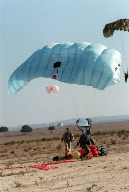 A member of the Sea-Air-Land (SEAL) Team lands in the drop zone during an Explosive Ordnance Disposal (EOD) Team/SEAL Team joint parachuting exercise near Naval Air Station, Rota, Spain