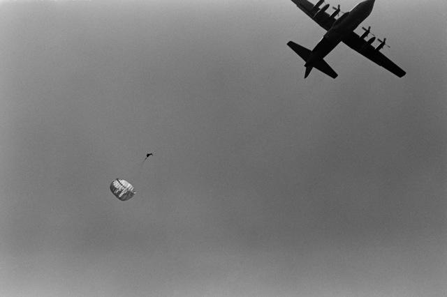 A member of the Sea-Air-Land (SEAL) Team parachutes toward the water from a C-130 Hercules aircraft during an Explosive Ordnance Disposal (EOD) Team/Sea-Air-Land (SEAL) Team joint parachuting exercise near Naval Air Station, Rota, Spain