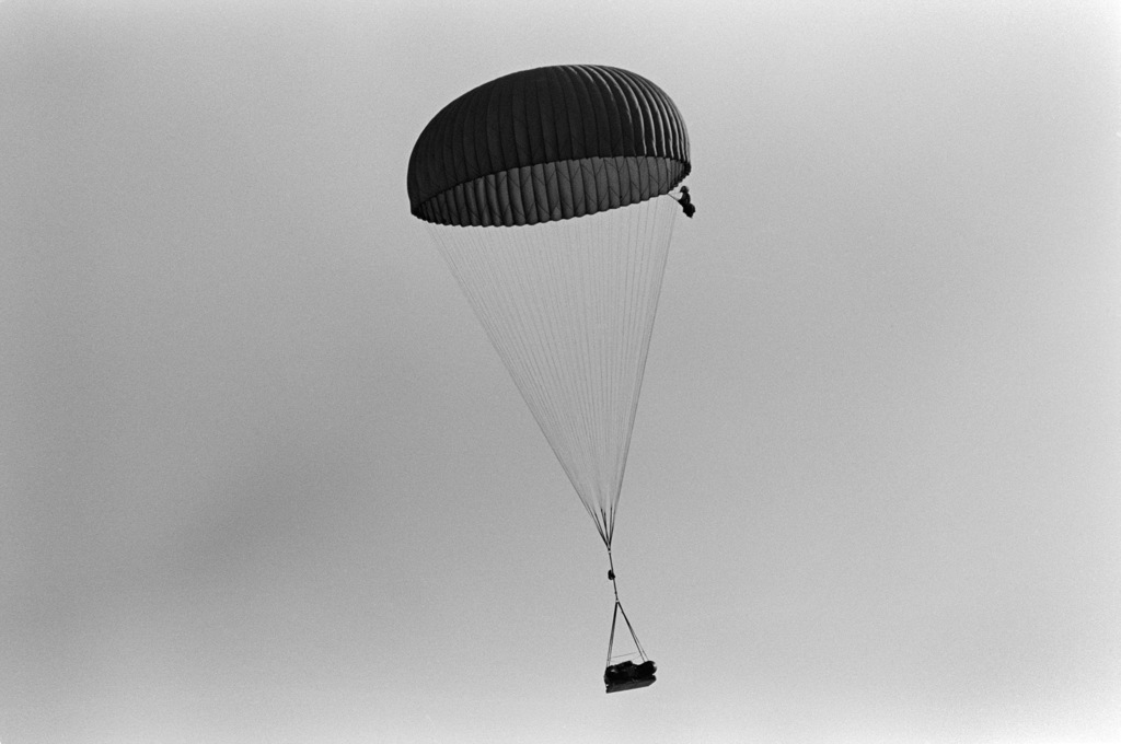 A parachute carrying airdropped equipment floats toward the water during an Explosive Ordnance Disposal (EOD) Team/Sea-Air-Land (SEAL) Team joint parachuting exercise near Naval Air Station, Rota, Spain