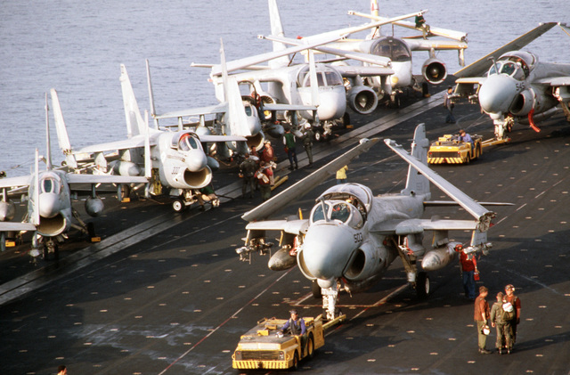 A-6E Intruder aircraft are towed by MD-3A tow tractors during flight operations aboard the aircraft carrier USS JOHN F. KENNEDY (CV 67). The ship is participating in NATO Exercise DISPLAY DETERMINATION '86