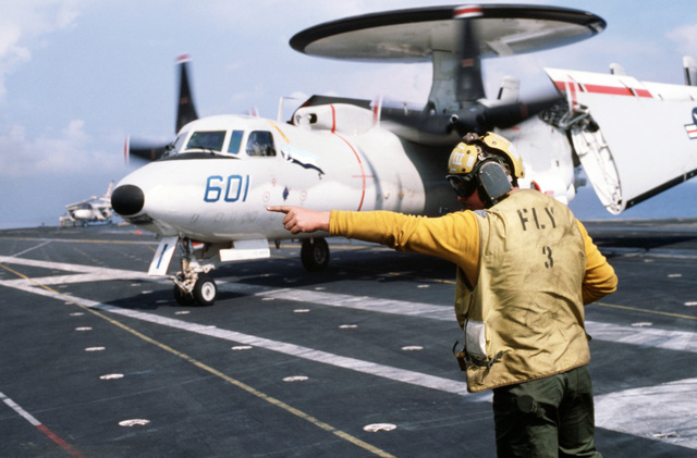 A plane director signals instructions to the pilot of an Airborne Early Warning Squadron 126 (VAW-126) E-2 Hawkeye aircraft during flight operations aboard the aircraft carrier USS JOHN F. KENNEDY (CV 67). The ship is participating in NATO Exercise DISPLAY DETERMINATION '86