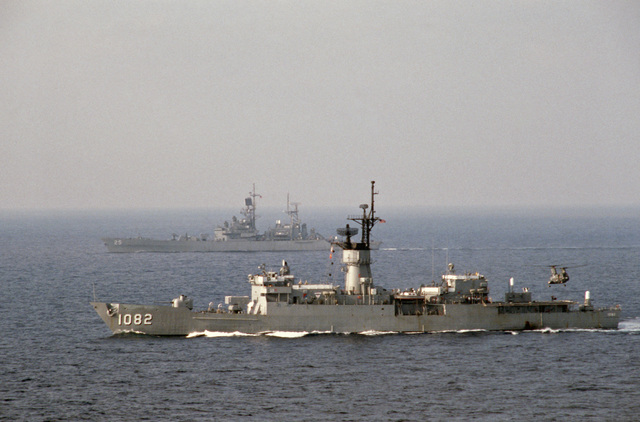 A port view of the frigate USS ELMER MONTGOMERY (FF 1082) and the nuclear-powered guided missile cruiser USS BAINBRIDGE (CGN 25) underway during NATO Exercise DISPLAY DETERMINATION '86. A CH-46 Sea Knight helicopter is hovering above the helicpopter pad of the Elmer Montgomery