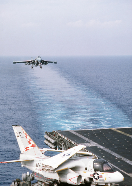 An A-6E Intruder aircraft approaches for a landing aboard the aircraft carrier USS JOHN F. KENNEDY (CV 67) during NATO Exercise DISPLAY DETERMINATION '86. An S-3A Viking aircraft is parked on the edge of the flight deck, foreground