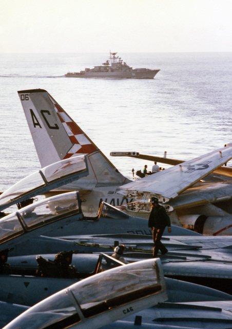 F-14A Tomcat aircraft are serviced on the flight deck of the aircraft carrier USS JOHN F. KENNEDY (CV 67) during NATO Exercise DISPLAY DETERMINATION '86. A Soviet Krivak class frigate is in the background, observing the exercise