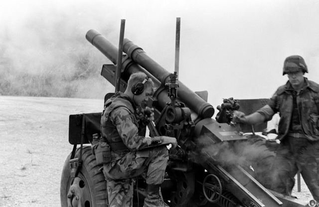 Assistant gunner Corporal (CPL) Kenneth Knigga opens the breech of an M102 105 mm howitzer as section chief CPL James Olson talks with the fire direction control center during a firing exercise at at Camp Hansen's Range 211