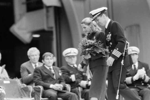 Captain (CAPT) Paul W. Parcells, commanding officer of the nuclear-powered aircraft carrier USS THEODORE ROOSEVELT (CVN 71), escorts Barbara W. Lehman, sponsor and wife of Secretary of the Navy John F. Lehman Jr., to her seat on the speakers platform during the ship's commissioning