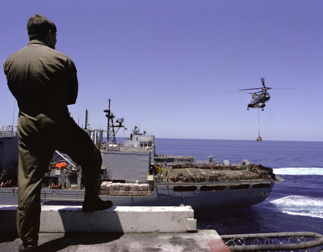 A crew member stands by on the flight deck of the nuclear-powered aircraft carrier USS CARL VINSON (CVN-70) as a Helicopter Combat Support Squadron 5 (HC-5) CH-46 Sea Knight helicopter approaches with supplies from the combat stores ship USS SAN JOSE (AFS-7) during a vertical replenishment operation