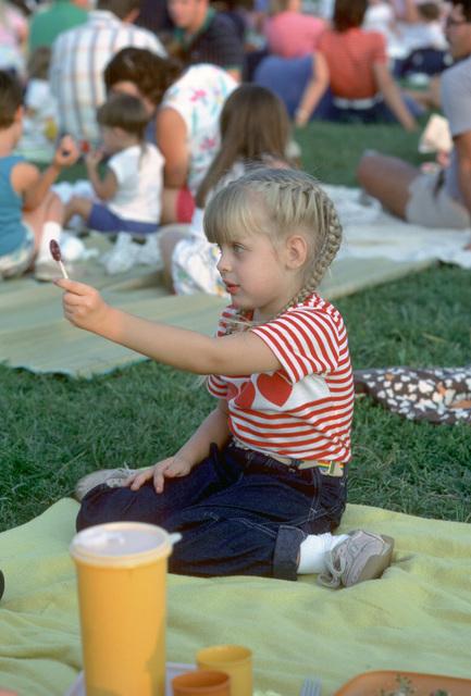 A little girl holding a lollipop awaits the start of the US Navy Band's Silver Anniversary Lollipop Concert