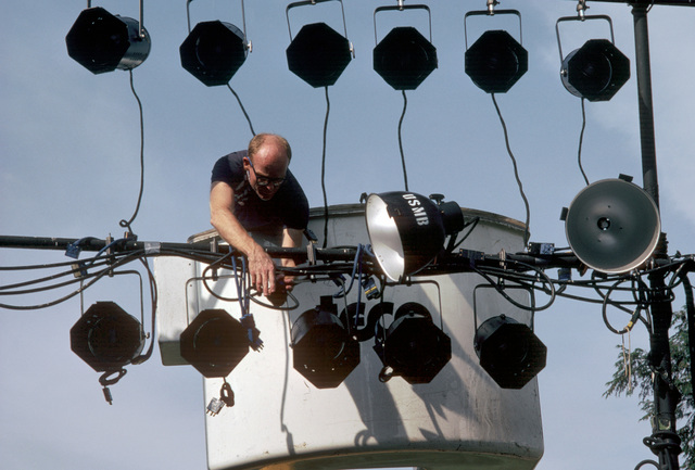 A member of the stage crew makes adjustments on lights for the US Navy Band's Silver Anniversary Lollipop Concert