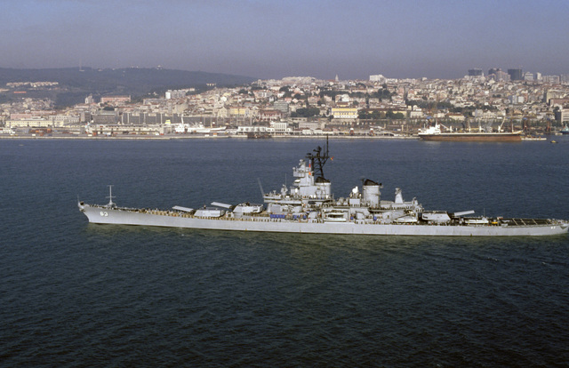A port beam view of the battleship USS MISSOURI (BB 63) departing Lisbon, Portugal.  The MISSOURI is on an around-the-world shakedown cruise
