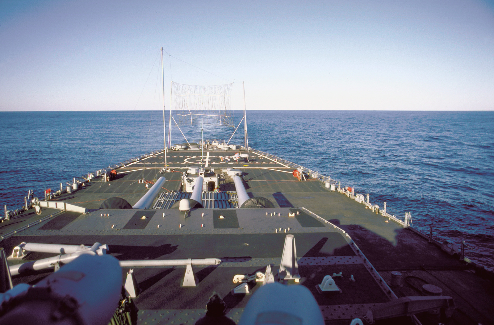 A view of the stern of the battleship USS IOWA (BB-61) with a Pioneer I remotely-piloted vehicle (RPV) in launching position and a recovery net erected on the ship's stern. The RPV, which carries a stabilized television camera and a laser designator, is being tested aboard the IOWA as a basic gunfire support system with over-the-horizon targeting and reconnaissance capabilities. The system may be operated out to a range of 110 miles from the battleship surface group and has an endurance of eight hours